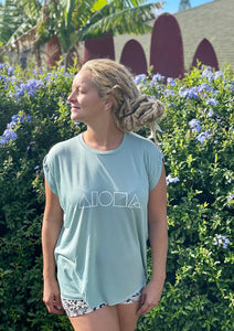 Woman with blond dreadlocks wearing Mauka to Makai womens muscle tee in Dusty blue with her face towards the sun