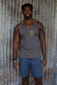 Man wearing Grey unisex tank top screen printed on front left chest with a circle logo showing words Maui with mountains above and fish below