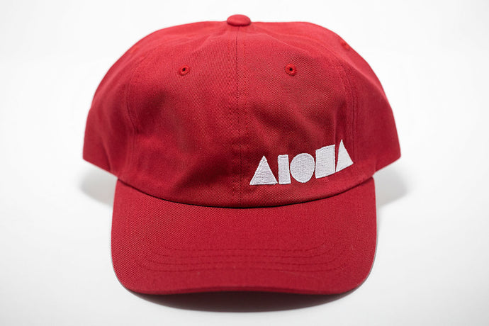 Red curved bill baseball cap (dad hat) embroidered with white Aloha Shapes ® logo