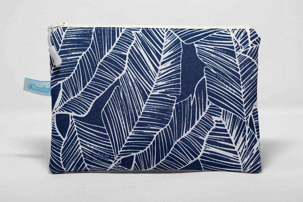 Handmade wet/dry clutch size bag with dark blue banana leaf print fabric outside and heavy duty white plastic inside