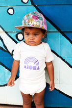 Baby girl wearing a Pink Pineapple Aloha Shapes hat in front of a graffiti wall
