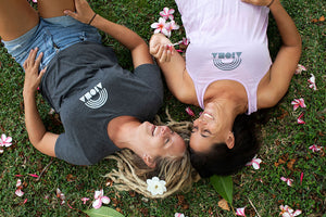 Two women laying down laughing in the grass with flowers in their hair and on the ground. Both wearing Aloha Shapes Rainbow designs