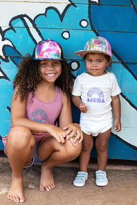 Baby wearing cream color onesie hand-screen printed on the front with our Aloha Shapes ® logo over a Hawaiian rainbow in metallic purple in front of a graffiti wall in Paia, Maui