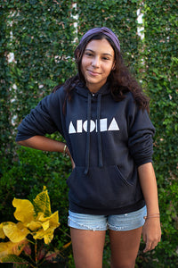 Young woman wearing Dark grey long sleeve pullover adult unisex hoodie hand screen printed in Maui on front chest with white Aloha Shapes logo
