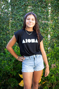 Young woman wearing Black Aloha Shapes® womens muscle tee tucked into cutoff jean shorts