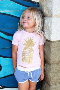 Young blond girl smiling in a Pink babies hand screen printed with a gold pineapple made of repeating Aloha Shapes logos. Handmade in Maui Hawaii