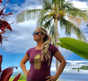 Blond dreadlocked girl standing under coconut palm tree wearing a Soley Aloha Pineapple womens tee