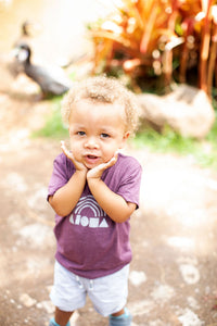 Cute little boy wearing maroon Aloha Shapes® rainbow toddler tee