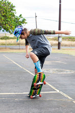 Young man riding a skateboard in Maui, Hawaii wearing camo Shapes youth baseball tee