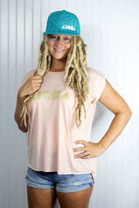 Blond dreadlocked girl wearing Aloha Shapes ® logo womens flowy muscle tee