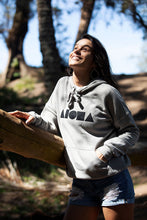 Young woman looking toward the sunshine in the woods wearing Heather stone colored unisex pullover hoodie with black Aloha Shapes® logo hand-screenprinted on front chest and torn up jean shorts. Handmade in Maui Hawaii