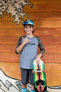 Young man holding a skateboard in Maui, Hawaii wearing camo Shapes youth baseball tee
