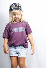 Cute young blond girl wearing backwards snapback hat and maroon aloha Shapes® logo youth tshirt