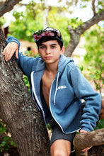 Young man sitting on a tree branch wearing an Aloha Shapes zip up hoodie unzipped and open with arm up on the tree