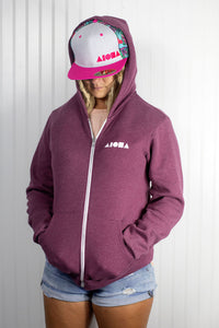 "Blond dreadlocked girl wearing Aloha Shapes ® logo ""Paradise pink"" snapback hat and zip-up hoodie"