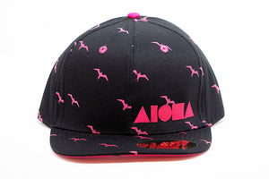 Adult flat brim snapback hat with black fabric and pink iwa bird pattern. Embroidered with neon pink Aloha Shapes ® logo