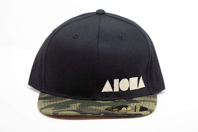 Black adult flat brim snapback hat embroidered with tan Aloha Shapes ® logo and a camo brim