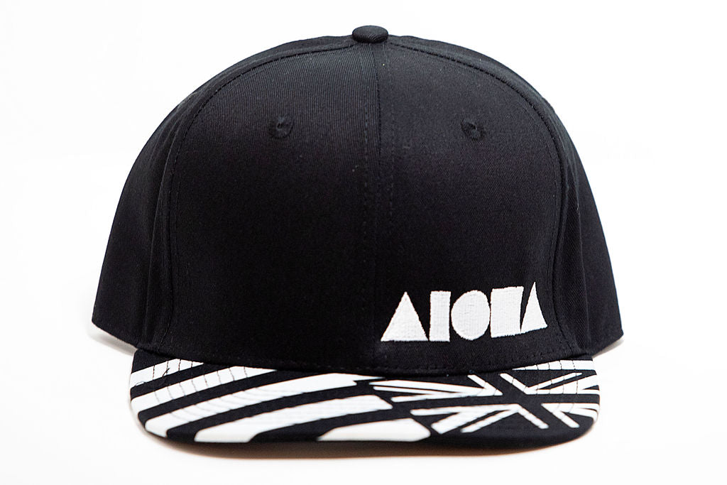 Black and white Hawaiian flag on adult flat brim snapback. Embroidered with white Aloha Shapes® logo