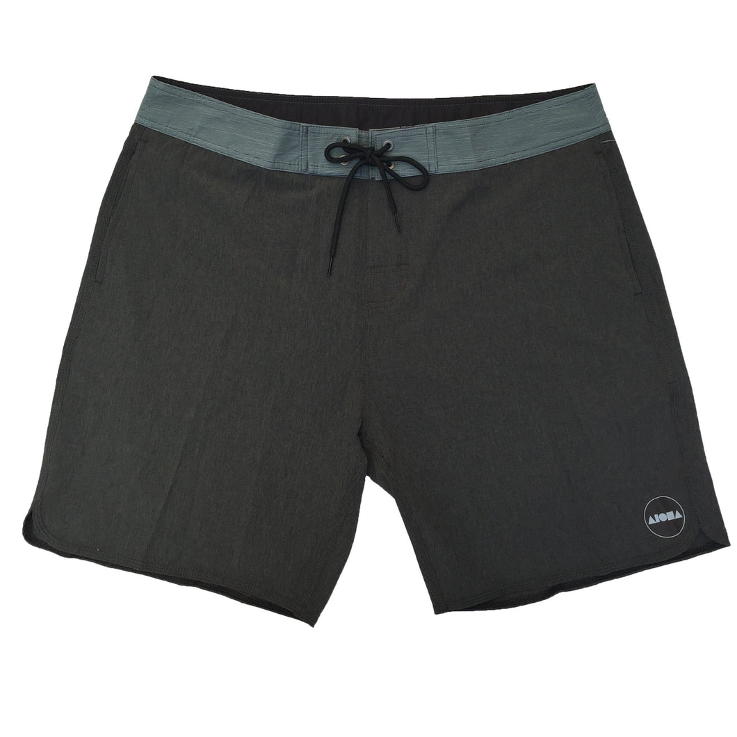 Mens grey surf board shorts with green waistband and pocket detail. Black drawstring. Black/white circle Aloha Shapes® logo on left short leg bottom