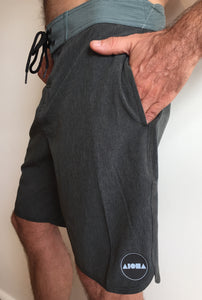 Close-up image of man wearing Aloha Surf Shapes board shorts with hand in pocket