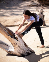 Woman stretching against a fallen tree on beach wearing Aloha Surf Shapes womens workout leggings