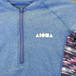 Detail of womens surf rash guard top zipper and Aloha Shapes® logo on front left chest