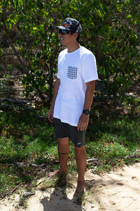 Man checking the surf on beach wearing white color unisex pocket tee with basketweave Aloha Shapes® design.