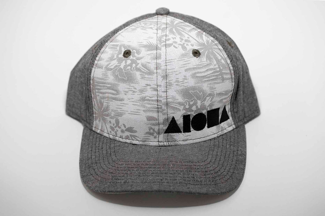 Grey denim and tropical palm tree print fabric Adult curved bill snapback hat embroidered in Maui Hawaii with black Aloha Shapes logo