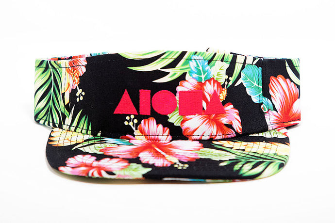 Tropical flower print visor embroidered in Maui, Hawaii with neon pink Aloha Shapes logo