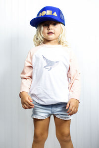 Cute young blond girl wearing humpback whale youth baseball tee and Aloha Shapes® youth trucker hat