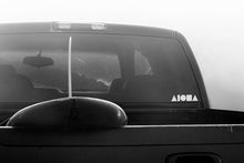 Black and white photo of a pickup truck with surfboard hanging out the back. White ALOHA Shapes ® logo decal sticker on back window of truck.