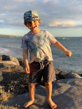 "Happy young child near the ocean wearing a ""Banana Bread"" youth snapback hat"