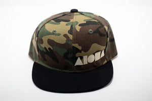 Youth Snapback hat with a camo print and black bill embroidered with beige Aloha Shapes ® logo