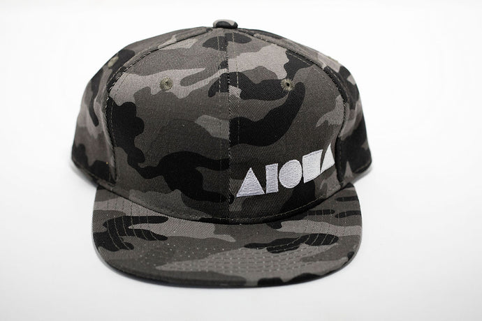 Youth Snapback hat with a greyscale camo print embroidered with white Aloha Shapes ® logo