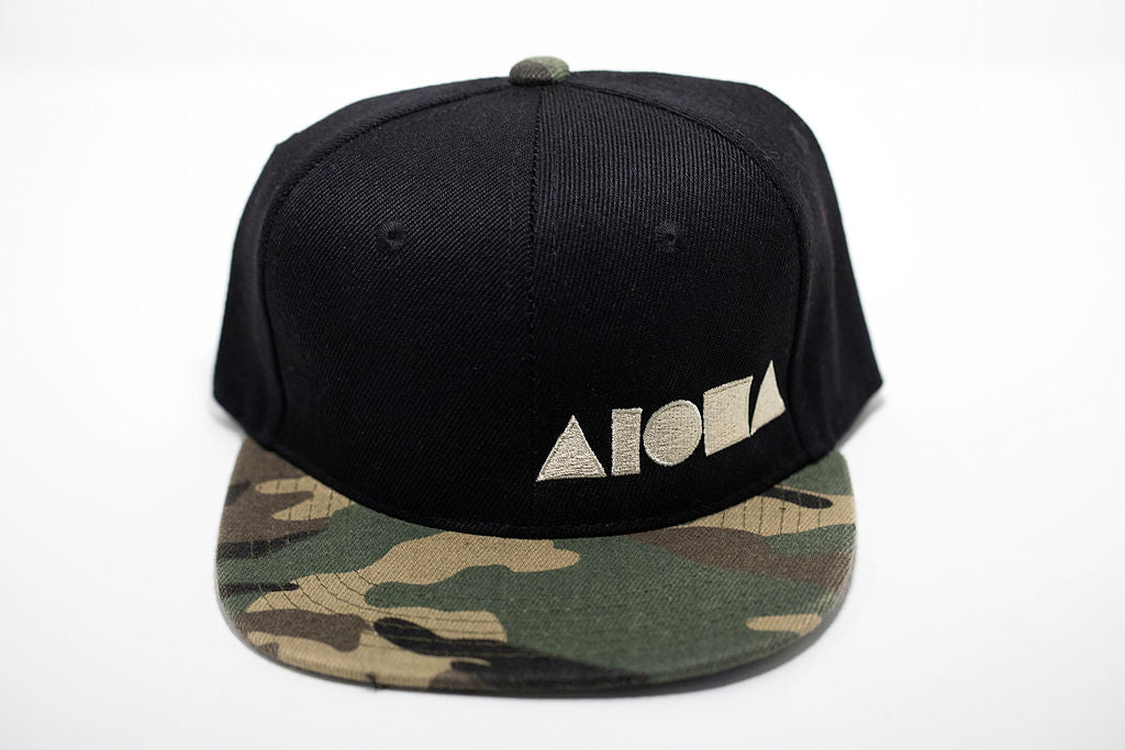 Camo print and black youth flat brim snapback hat embroidered with off-white Aloha Shapes ® logo
