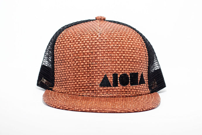Youth flat brim snapback hat with burnt orange straw front, black mesh back panels. Embroidered with black Aloha Shapes logo on front.