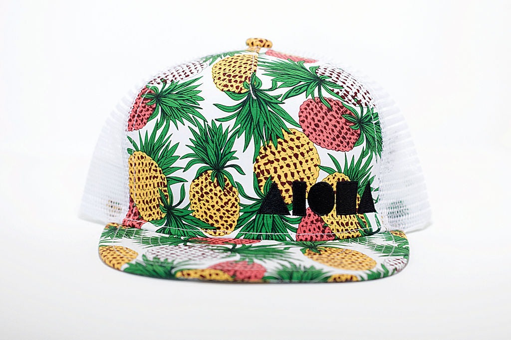Adult flat brim snapback with tropical pineapple print fabric on front and white mesh back panels on back. Embroidered with black Aloha Shapes logo on front
