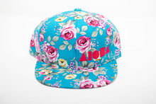 Youth flat brim snapback hat. Blue/pink/yellow floral print with roses all over hat. Embroidered with pink ALOHA Shapes ® logo