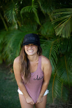 Young woman with a big beautiful smile wearing an Aloha Shapes ® black sparkly trucker hat