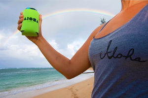 Girl holding an Aloha Shapes ® logo koozie on the beach in front of a rainbow