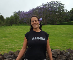 Woman with flowers in her hair wearing a Black Aloha Shapes ® flowy muscle tee in front of jacaranda tress