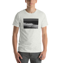 Person wearing jeans and Ash grey unisex T-shirt printed on the front with a black and white photo by Stu Soley of the waves at Uluwatu, Bali