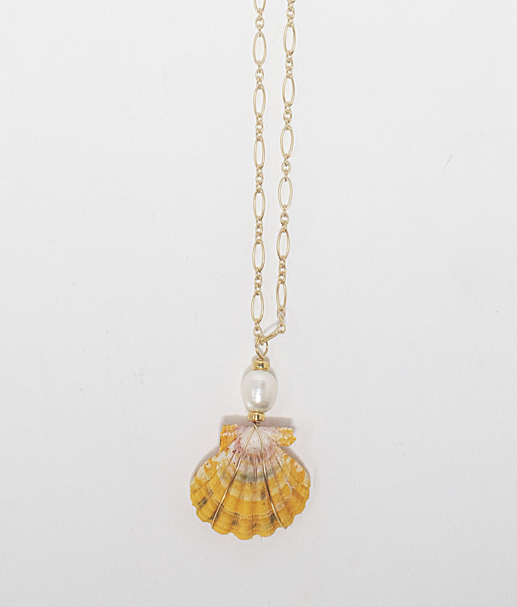 Hawaiian sunrise shell wire-wrapped with freshwater pearl bead hanging from 14 karat gold fill chain. Handmade in Maui, Hawaii