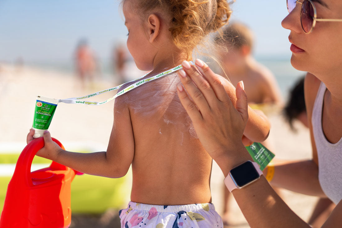 Mum putting sunscreen on child while he holds it