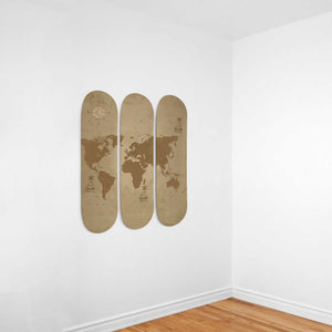 Map Out Your Adventure - 3 Skateboard Wall Art hung on a white wall with wooden flooring