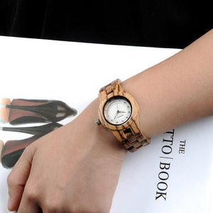 Zebra Wood Watch with Rhinestone Dial on a ladies arm while she holds a book