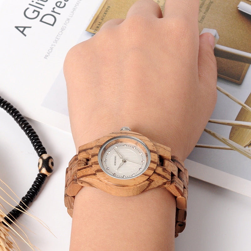 Zebra Wood Watch with Rhinestone Dial on a ladies arm while she rest her hand next to a design book
