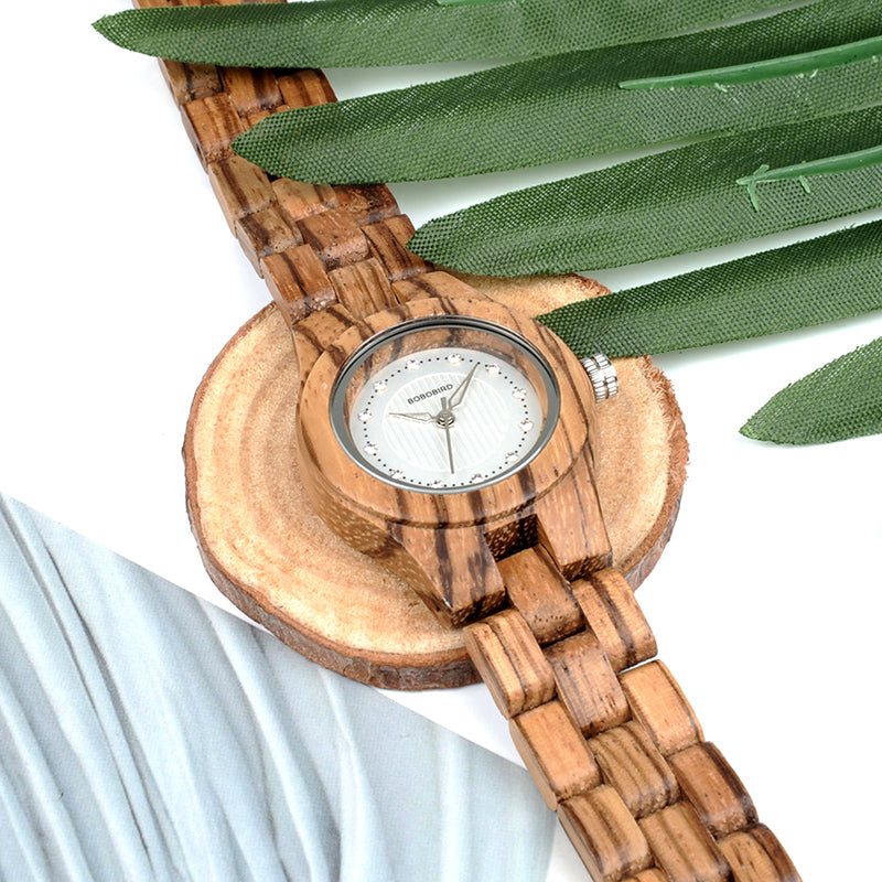 Zebra Wood Watch with Rhinestone Dial. placed next to green leaves