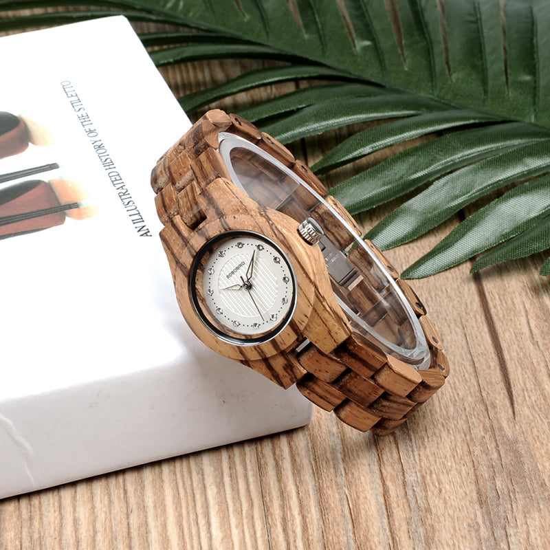 Zebra Wood Watch with Rhinestone Dial resting against a book