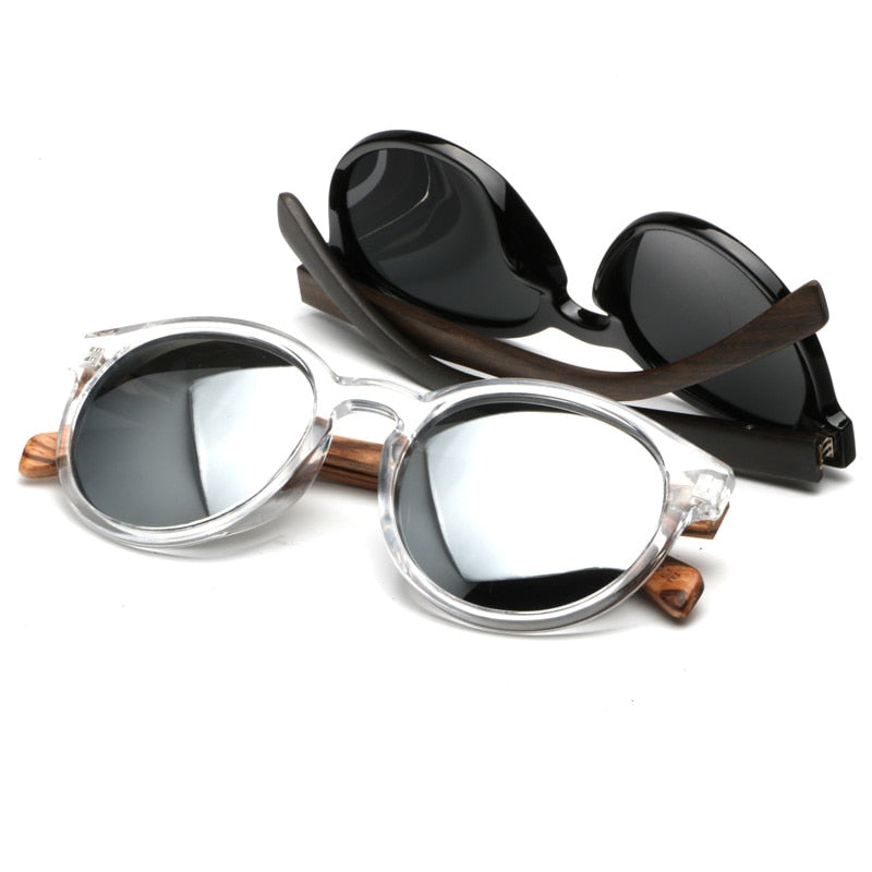 Vintage silver frames with natural wooden arms and grey lens with the vintage balck sunglasses resting in the background on a white background